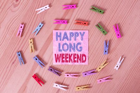 Conceptual hand writing showing Happy Long Weekend. Concept meaning wishing someone happy vacation Travel to holiday Colored crumpled papers wooden floor background clothespin