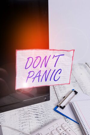 Text sign showing Don T Panic. Business photo text to avoid sudden uncontrollable fear or anxiety Keep calm Note paper taped to black computer screen near keyboard and stationary
