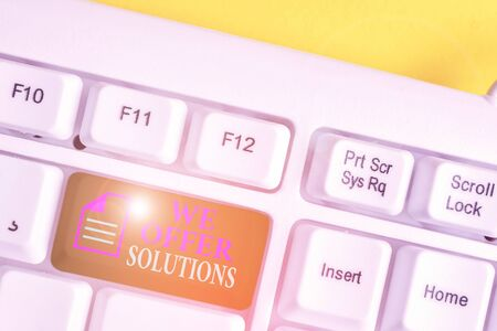 Writing note showing We Offer Solutions. Business concept for Offering help assistance Experts advice strategies ideas White pc keyboard with note paper above the white background