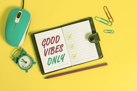 Word writing text Good Vibes Only. Business photo showcasing Just positive emotions feelings No negative energies Locked diary sheets clips marker mouse alarm clock colored background