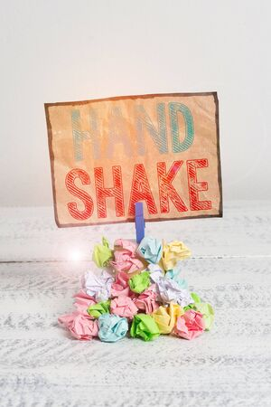 Handwriting text writing Hand Shake. Conceptual photo an act showing that you have made an agreement or greeting Reminder pile colored crumpled paper clothespin reminder white wooden space