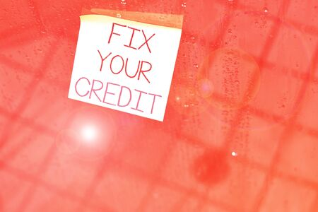 Writing note showing Fix Your Credit. Business concept for Keep balances low on credit cards and other credit Square paper piece notation stick to textured glass window Stockfoto
