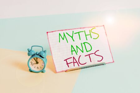 Handwriting text writing Myths And Facts. Conceptual photo Oppositive concept about modern and ancient period Mini size alarm clock beside a Paper sheet placed tilted on pastel backdrop