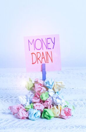 Writing note showing Money Drain. Business concept for To waste or squander money Spend money foolishly or carelessly Reminder pile colored crumpled paper clothespin wooden space