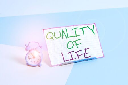 Handwriting text writing Quality Of Life. Conceptual photo being in good health decent job Enjoying every moment Mini size alarm clock beside a Paper sheet placed tilted on pastel backdrop