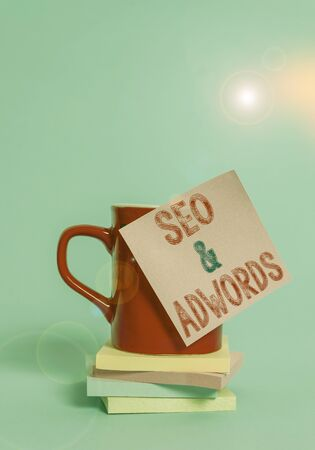 Conceptual hand writing showing Seo And Adwords. Concept meaning Pay per click Digital marketing Google Adsense Coffee cup colored sticky note stacked pads plain background