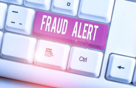 Writing note showing Fraud Alert. Business concept for security alert placed on credit card account for stolen identity White pc keyboard with note paper above the white background
