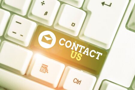 Conceptual hand writing showing Contact Us. Concept meaning Term used to describe reaching out with the business or demonstrating White pc keyboard with note paper above the white background