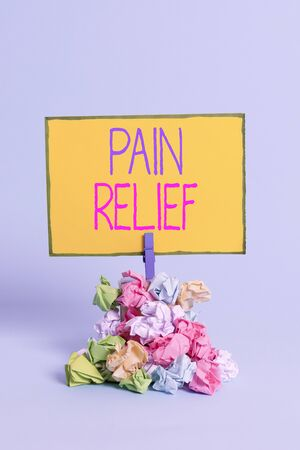 Text sign showing Pain Relief. Business photo showcasing Drugs or other methods of reducing or getting rid of pain Reminder pile colored crumpled paper clothespin reminder blue background