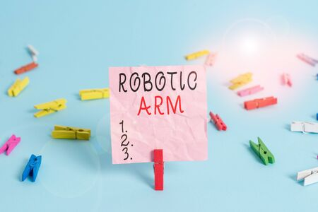 Handwriting text Robotic Arm. Conceptual photo programmable mechanical arm with similar function of a huanalysis arm Colored clothespin rectangle square shaped paper light blue background