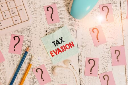 Writing note showing Tax Evasion. Business concept for the failure to pay or the deliberate underpayment of taxes Writing tools and scribbled paper on top of the wooden table Stock Photo