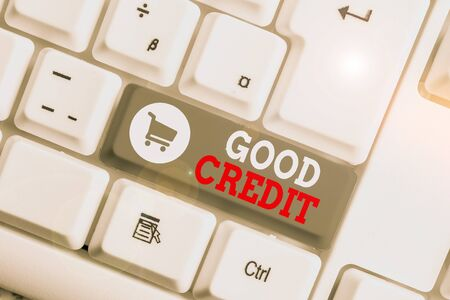 Conceptual hand writing showing Good Credit. Concept meaning borrower has a relatively high credit score and safe credit risk White pc keyboard with note paper above the white background