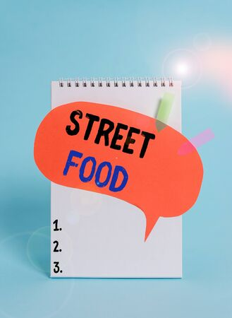 Text sign showing Street Food. Business photo text cooked food sold by vendors in a street or other public location Spiral notepad speech bubble arrow banners lying cool pastel background