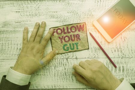 Text sign showing Follow Your Gut. Business photo text Listen to intuition feelings emotions conscious perception Hand hold note paper near writing equipment and modern smartphone device
