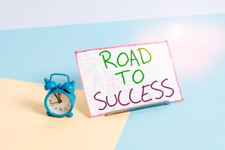 Handwriting text writing Road To Success. Conceptual photo studying really hard Improve yourself to reach dreams wishes Mini size alarm clock beside a Paper sheet placed tilted on pastel backdrop
