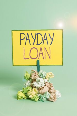 Text sign showing Payday Loan. Business photo showcasing Something lent or furnished on condition being returned Reminder pile colored crumpled paper clothespin reminder blue background