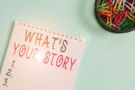 Writing note showing What S Your Story. Business concept for asking someone tell me about himself Share experience Blank empty notebook and stationary placed above pastel colour backdrop