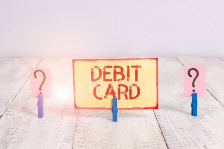 Text sign showing Debit Card. Business photo text card that deducts money directly from a demonstrating s is checking account Scribbled and crumbling sheet with paper clips placed on the wooden table Stok Fotoğraf - 133730044