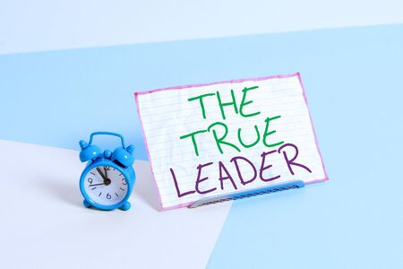 Handwriting text writing The True Leader. Conceptual photo one that move and encourage group of showing Responsibility Mini size alarm clock beside a Paper sheet placed tilted on pastel backdrop 写真素材