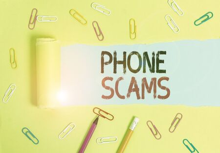 Word writing text Phone Scams. Business photo showcasing use of telecommunications for illegally acquiring money Stationary and torn cardboard placed above a plain pastel table backdrop