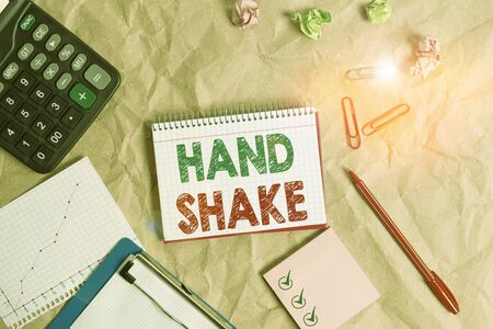 Word writing text Hand Shake. Business photo showcasing an act showing that you have made an agreement or greeting Papercraft craft paper desk square spiral notebook office study supplies