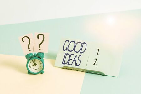 Writing note showing Good Ideas. Business concept for nice formulated thought or opinion Best possible course of action Alarm clock beside a Paper sheet placed on pastel backdrop
