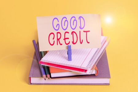 Conceptual hand writing showing Good Credit. Concept meaning borrower has a relatively high credit score and safe credit risk Book pencil rectangle shaped reminder notebook clothespins