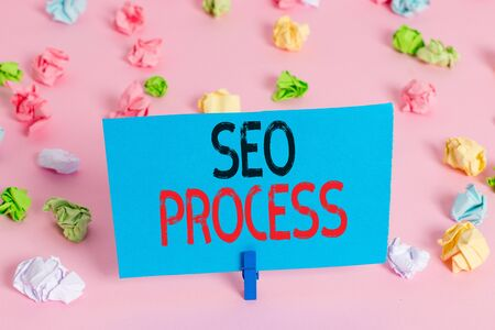 Handwriting text Seo Process. Conceptual photo steps of increasing the quality and quantity of website traffic Colored crumpled papers empty reminder pink floor background clothespin