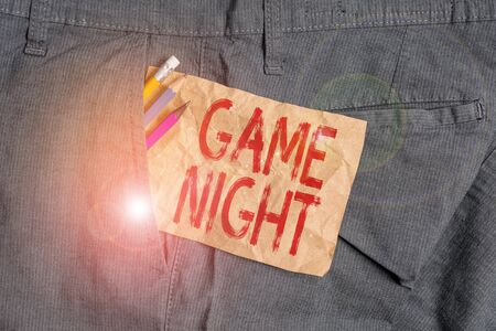 Word writing text Game Night. Business photo showcasing event in which folks get together for the purpose of getting laid Writing equipment and brown note paper inside pocket of man work trousers