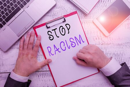 Word writing text Stop Racism. Business photo showcasing end the antagonism directed against someone of a different race Hand hold writing equipment tool near modern high technology laptop device