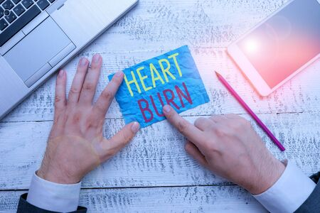 Conceptual hand writing showing Heart Burn. Concept meaning a burning sensation or pain in the throat from acid reflux Hand hold note paper near writing equipment and smartphone Stock Photo
