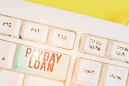 Conceptual hand writing showing Payday Loan. Concept meaning Something lent or furnished on condition being returned White pc keyboard with note paper above the white background