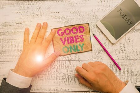 Text sign showing Good Vibes Only. Business photo text Just positive emotions feelings No negative energies Hand hold note paper near writing equipment and modern smartphone device