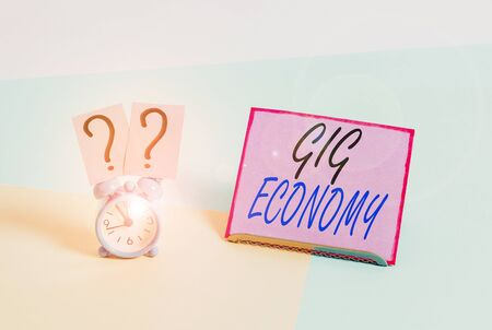 Word writing text Gig Economy. Business photo showcasing free market system in which temporary positions are common Mini size alarm clock beside a Paper sheet placed tilted on pastel backdrop