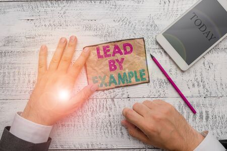 Text sign showing Lead By Example. Business photo text Be a mentor leader follow the rules give examples Coach Hand hold note paper near writing equipment and modern smartphone device