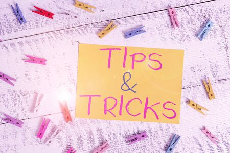 Conceptual hand writing showing Tips And Tricks. Concept meaning Steps Lifehacks Handy advice Recommendations Skills Colored clothespin rectangle shaped paper blue background