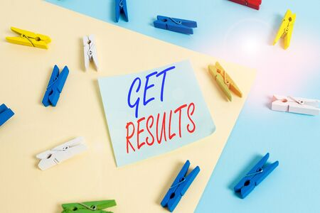 Text sign showing Get Results. Business photo showcasing to proceed or arise as a consequence effect or conclusion Colored clothespin paper empty reminder yellow blue floor background office