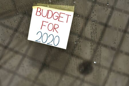 Writing note showing Budget For 2020. Business concept for An written estimates of income and expenditure for 2020 Square paper piece notation stick to textured glass window