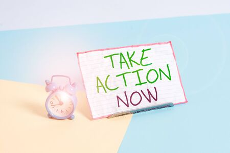 Handwriting text writing Take Action Now. Conceptual photo asking someone to start doing Good perforanalysisce Encourage Mini size alarm clock beside a Paper sheet placed tilted on pastel backdrop