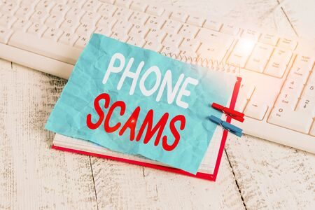 Word writing text Phone Scams. Business photo showcasing use of telecommunications for illegally acquiring money notebook paper reminder clothespin pinned sheet white keyboard light wooden Stok Fotoğraf