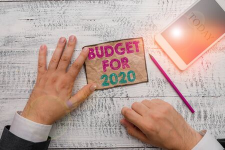 Text sign showing Budget For 2020. Business photo text An written estimates of income and expenditure for 2020 Hand hold note paper near writing equipment and modern smartphone device