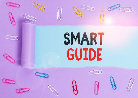 Conceptual hand writing showing Smart Guide. Concept meaning used to guide the development of measurable goals to attain Paper clip and torn cardboard on wood classic table backdrop