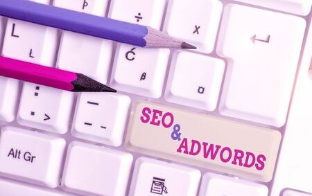 Writing note showing Seo And Adwords. Business concept for Pay per click Digital marketing Google Adsense White pc keyboard with note paper above the white background Banco de Imagens