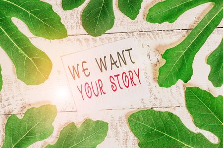 Conceptual hand writing showing We Want Your Story. Concept meaning Tell Us something a Glimpse About Your Life History Leaves surrounding notepaper above a classic wooden table Archivio Fotografico