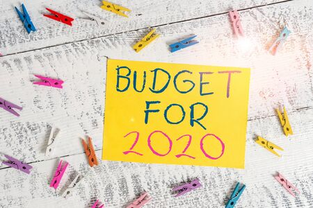 Conceptual hand writing showing Budget For 2020. Concept meaning An written estimates of income and expenditure for 2020 Colored clothespin rectangle shaped paper blue background