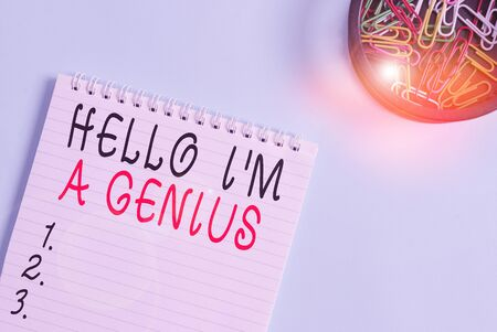 Writing note showing Hello I M A Genius. Business concept for Introduce yourself as over average demonstrating to others Blank empty notebook and stationary placed above pastel colour backdrop