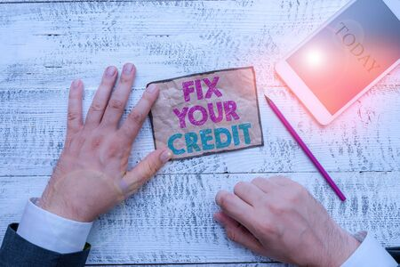 Text sign showing Fix Your Credit. Business photo text Keep balances low on credit cards and other credit Hand hold note paper near writing equipment and modern smartphone device