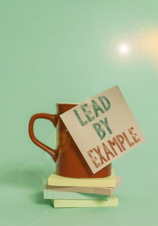 Conceptual hand writing showing Lead By Example. Concept meaning Be a mentor leader follow the rules give examples Coach Coffee cup colored sticky note stacked pads plain background