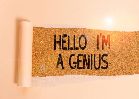 Conceptual hand writing showing Hello I M A Genius. Concept meaning Introduce yourself as over average demonstrating to others Cardboard which is torn placed above a wooden classic table