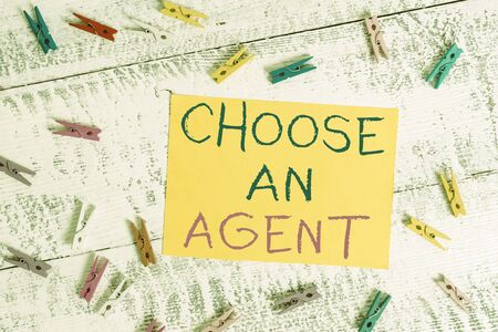 Conceptual hand writing showing Choose An Agent. Concept meaning Choose someone who chooses decisions on behalf of you Colored clothespin rectangle shaped paper blue background